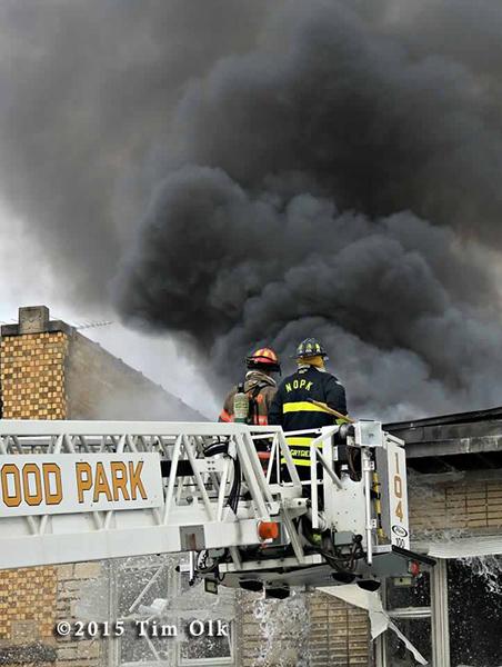 firemen in tower ladder bucket fight fire with huge smoke