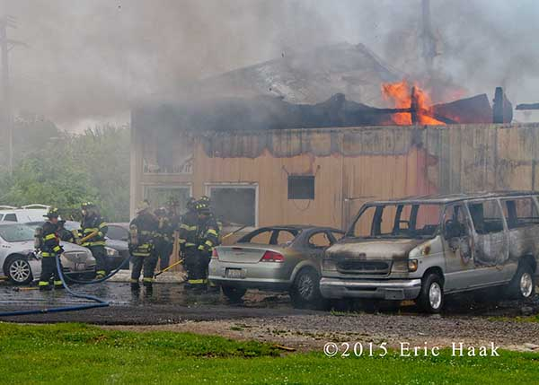 flames through the roof of an auto body shop