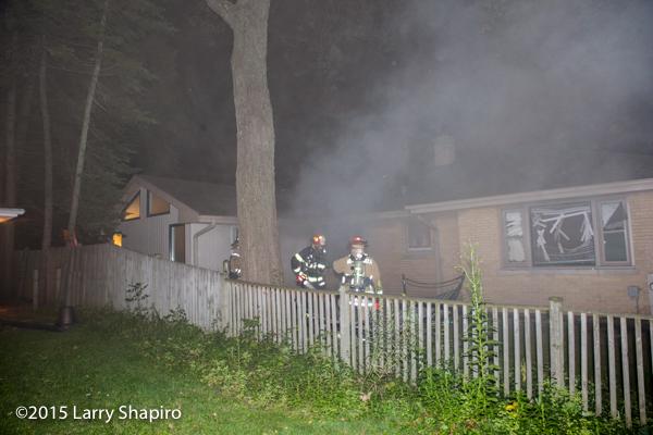 firemen at night fire scene with smoke