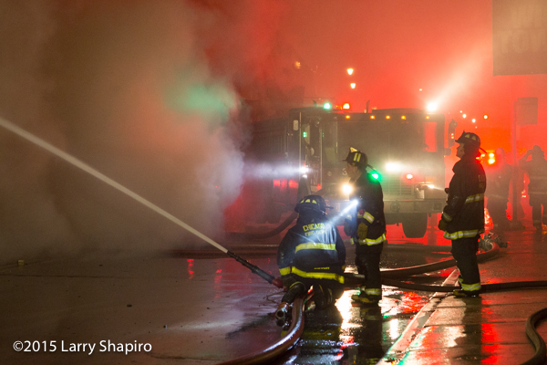 firemen silhouetted at night fire scene