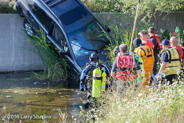 fire department divers view a car on a retaining wall with the driver inside