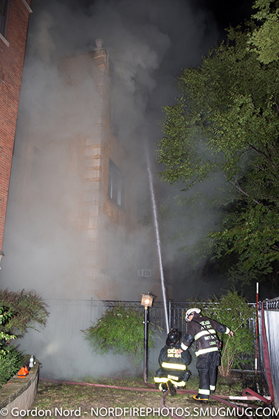 firefighter with hose line at night