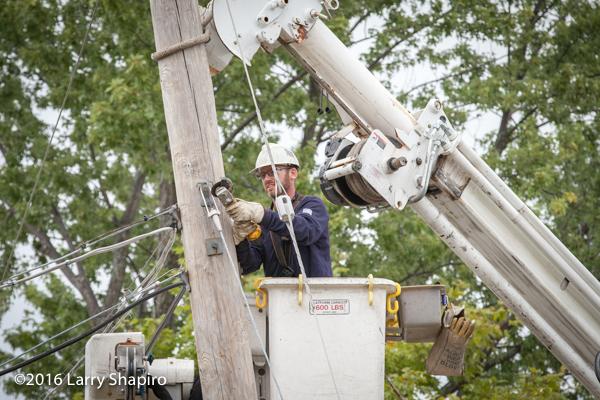 lineman secures utility pole