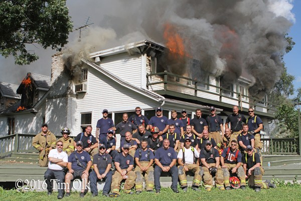 firefighters pose with burning building