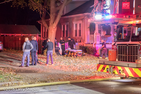 gurney near paramedics working on fire victim