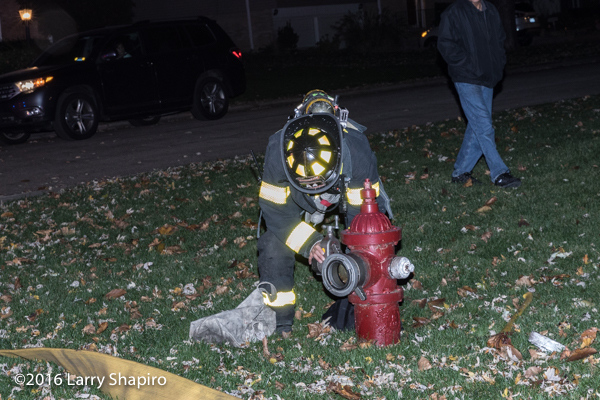 firefighter hooks hose to hydrant at night