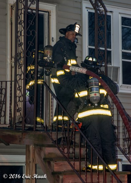 firefighters enter a house with a hose line