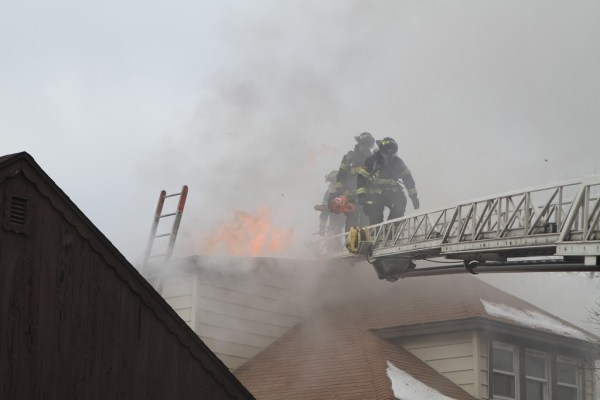 Firefighters on aerial ladder with flames