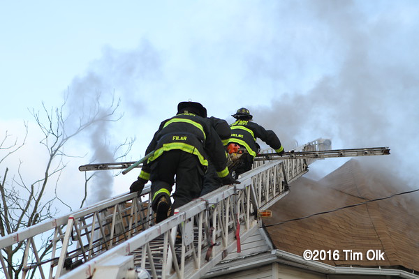 Firefighters climbing aerial ladder