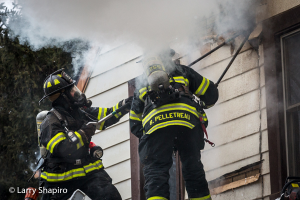 Firefighters use pike poles to ventilate house on fire