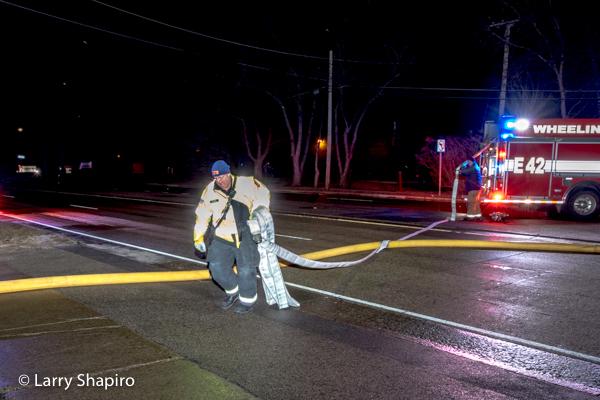 Firefighter pulls hose across the street