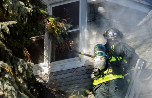 firefighter breaks window with pike pole