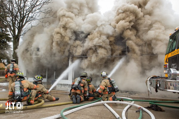 firefighters in street battle fire with which smoke