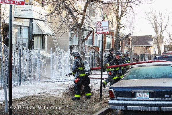 firefighters move hose at winter fire