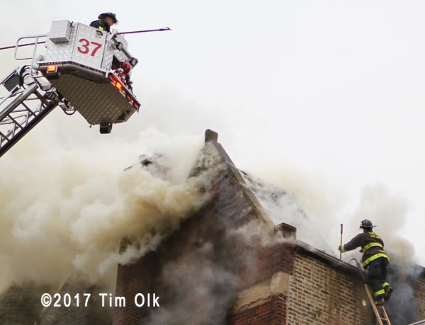heavy smoke from roof to townhouse on fire