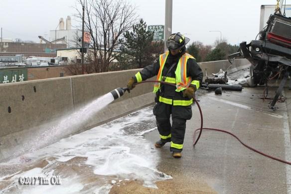 firefighter applies foam after crash on highway
