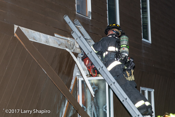 Firefighter cuts siding on a house