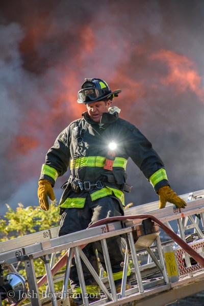 firefighter descends aerial ladder with fire