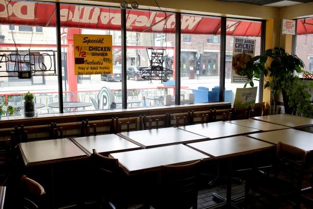 Tables and chairs are placed near windows at Wrigleyville Dog in the Wrigleyville neighborhood near the Chicago Cubs home stadium of Wrigley Field