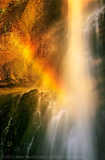 Sunlight forms a rainbow at the base of Multnomah Falls in Corbett, Oregon