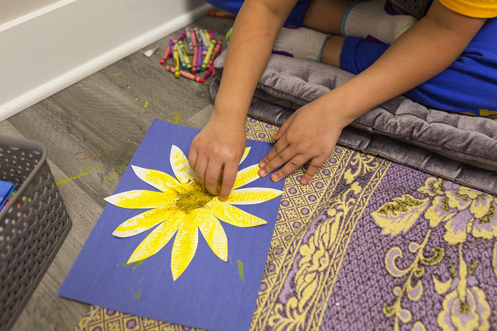 An eight-year-old participant colors jasmine flower cutouts.