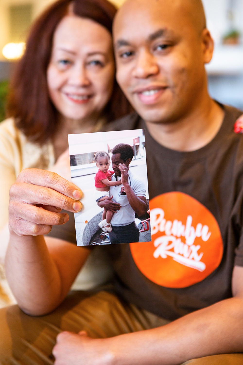 Chef Chris Reed with his mother, Priscilla. Chris holds a photo of his late father, Donald, carrying him as a child.