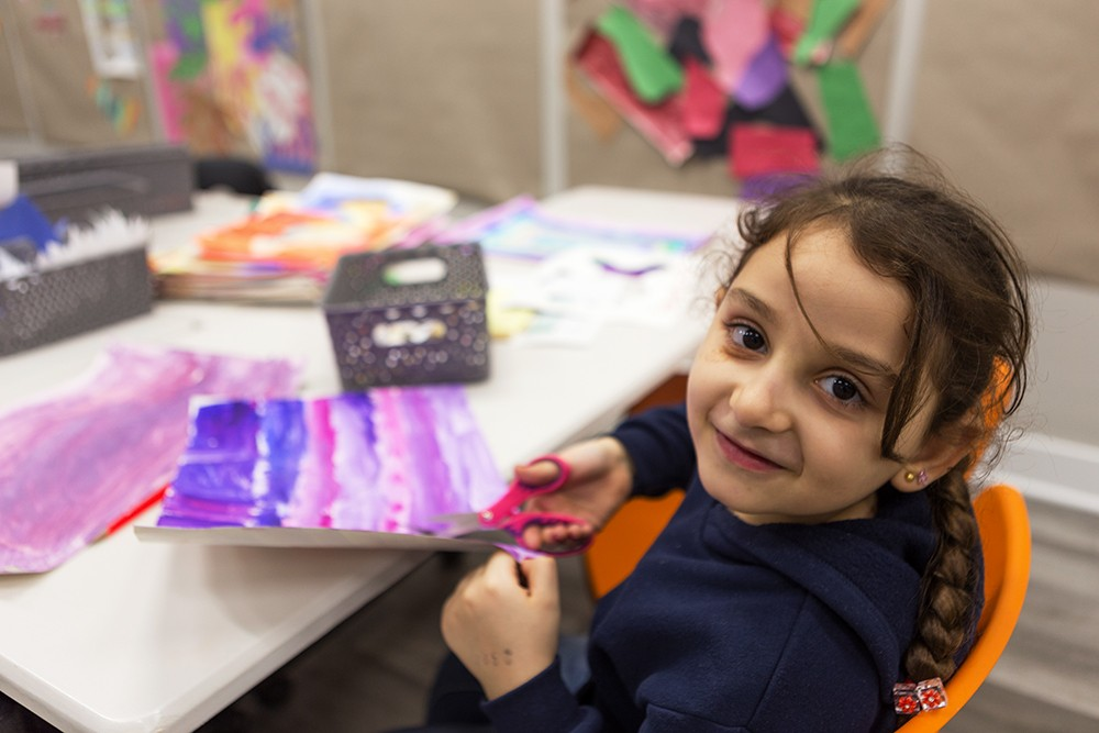 Fatima, 6, cuts out shapes of jasmine leaves from watercolor drawings she created. Fatima and her family moved to Chicago from Syria about three years ago.