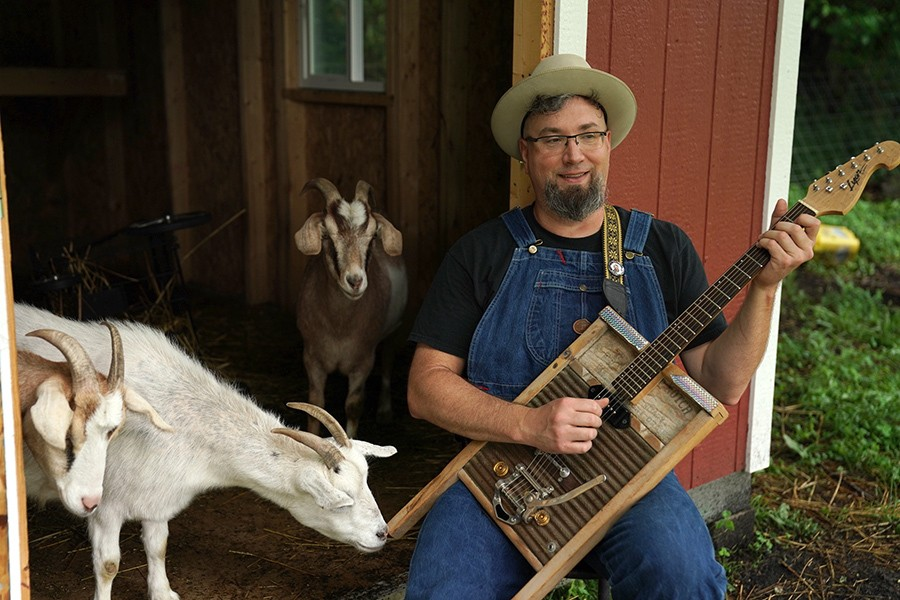 A goat takes an interest in Leise's washboard guitar.