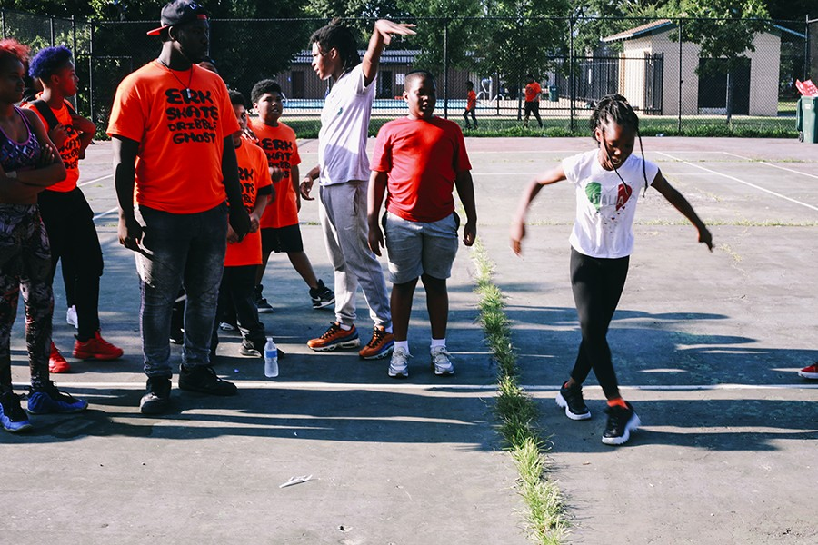 """Instructor Sterling """"Steelo"""" Lofton (third from right) and several campers look on while a student shows off her footwork moves."""