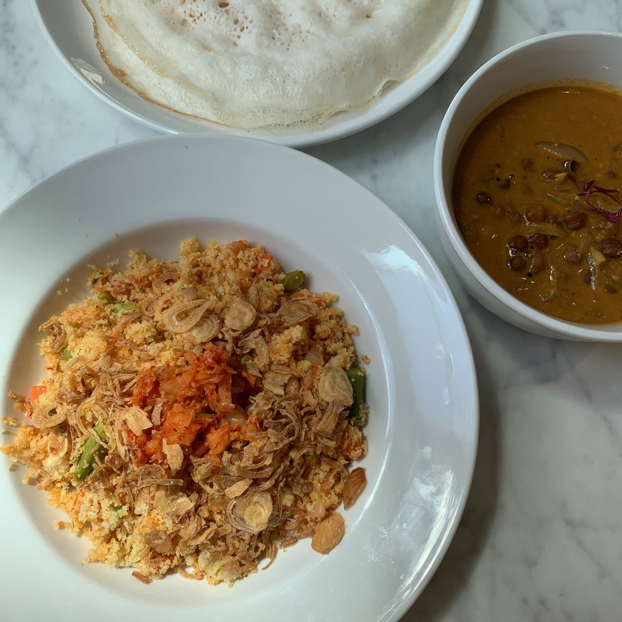 (counterclockwise from bottom) Kimchi upma, kadala curry, and <i>appam</i>, crepes made with fermented rice flour and coconut milk