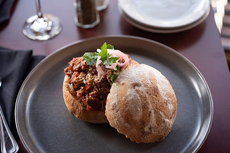 <i>Leskovačka mućkalica</i> (pork stew) in a branded sourdough boule