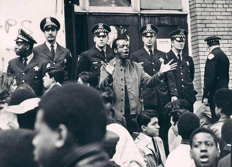 A city youth welfare street worker pleads with students to go home after a walkout at Harrison High school on October 9, 1968. Police line the school entrance.