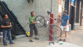 Jason Jenkins demonstrates how to change a tire at the Paramount Room's new bike fix-it station