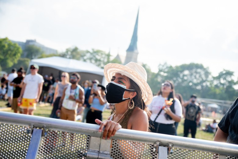 Twenty-two-year-old Gisselle Lydia Salgado wears two masks in Union Park on Friday, August 20, as she listens to Chicago artist Kaina perform at Ruido Fest.