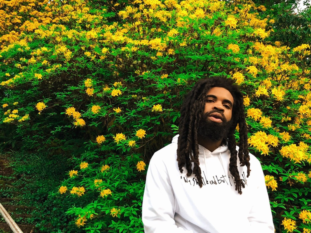 Pivot Gang DJ and producer Squeak in front of a bush covered in brilliant yellow flowers