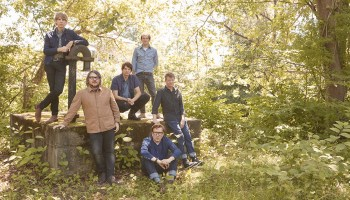 The band Wilco posing for a photo in the woods in 2021.