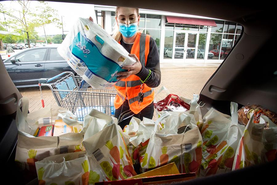 The Scholars Slide By volunteer Korrina Zartler loads groceries for delivery.