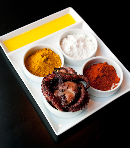 Olive-oil-slicked octopus tentacles accompanied by Peruvian yellow chile powder, coconut powder, and smoked paprika-tomato powder.