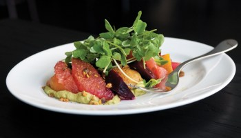 A salad of roasted beets, spiced pistachio, and grapefruit is set atop a cool avocado puree.