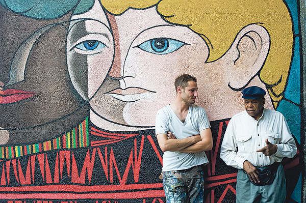 Artists Nicholas Kashian and William Walker in front of Walker's mural <i>Childhood Without Prejudice</i>, on the Illinois Central viaduct at 56th Street, which Kashian recently restored