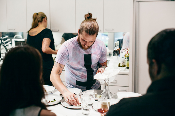 Baltzley's May pop-up dinner at the home of the parents of his wife, Leigh Hansen (standing behind him), was a tribute to the menu he conceived—but never got to execute—at Tribute.