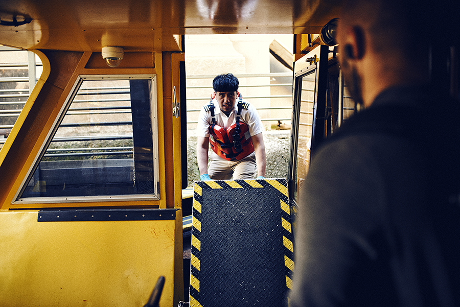 Deckhand Nick Leon installs a nonslip ramp for passengers to enter and exit the ship.