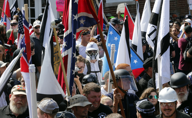 White nationalist demonstrators walk into the entrance of Lee Park surrounded by counter demonstrators Saturday in Charlottesville, Virginia.