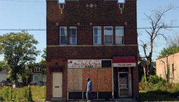 A pedestrian walks past a boarded-up hair salon on the 7200 block of South Ashland in Englewood last September.