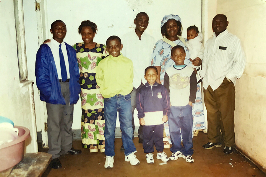 Bugumba with his parents and his six siblings in 2004, in the family's first apartment in Johannesburg, South Africa. His mother and father are at upper right, and Bugumba stands in front of his mother, in a white shirt with black sleeves.