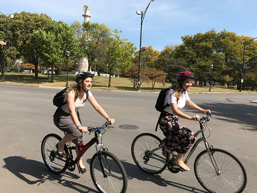 Amanda Aamodt and Emily McCrary biking near Logan Square's Mormon church
