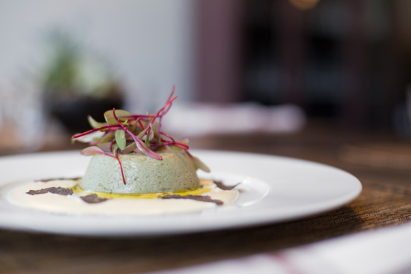 A molded flan of emulsified artichokes and asparagus rests on a rich puree of fontina cheese, cream, eggs, and butter.