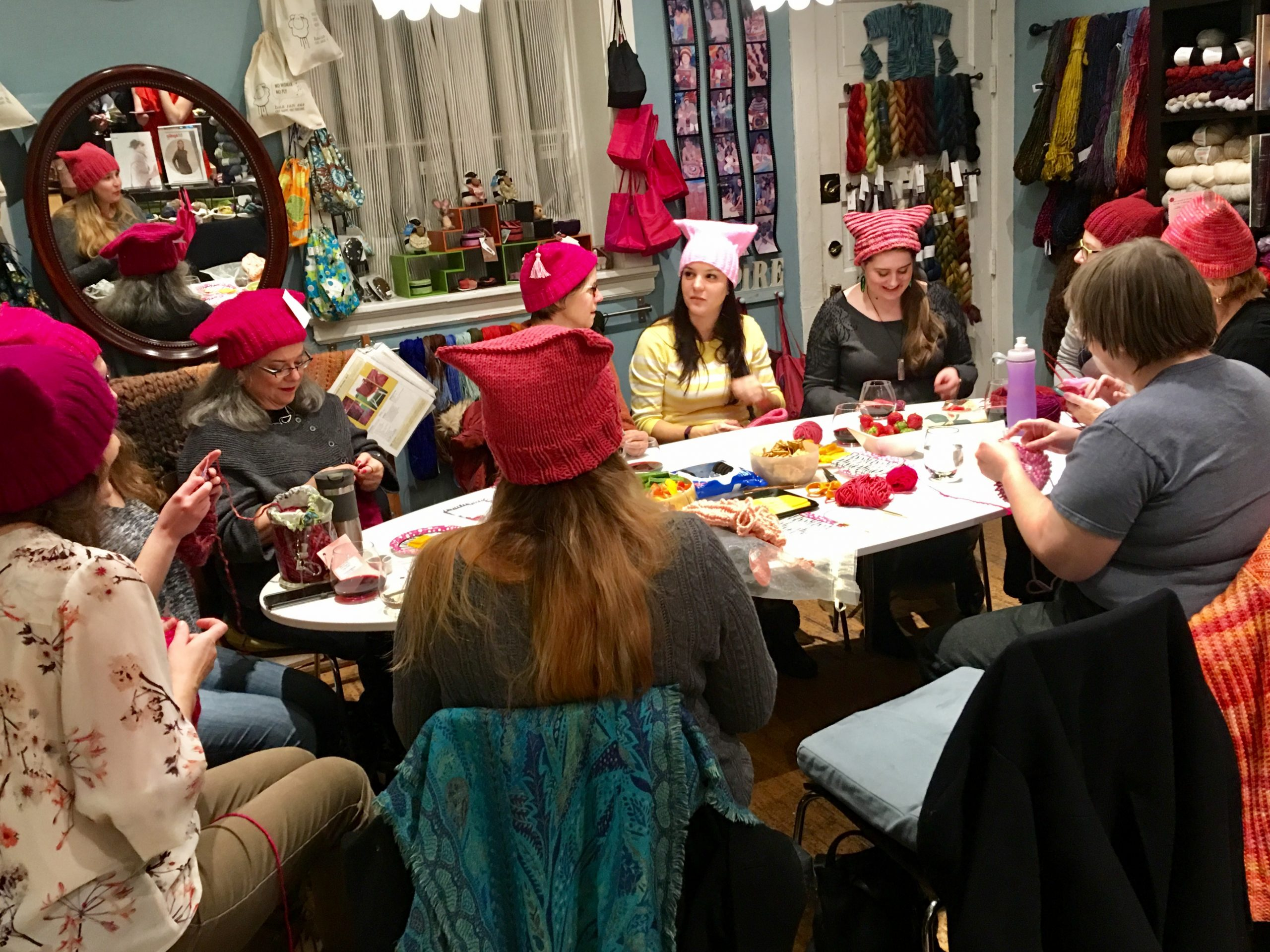Sister Arts friends and customers knit pussyhats at the 'Marcher Send-Off Party.'