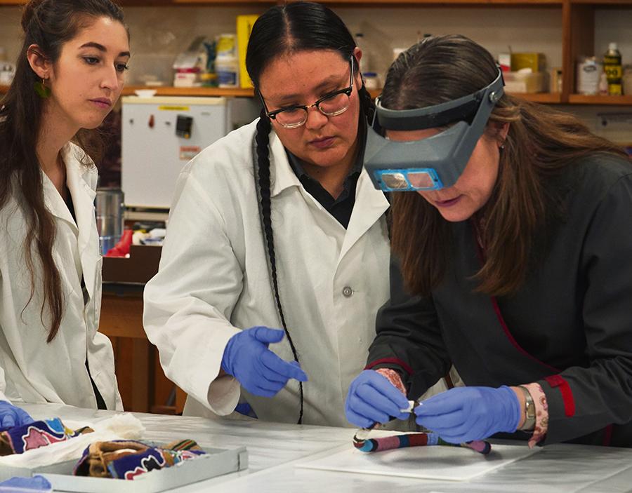 Lead conservator Stephanie Hornbeck (right) with conservation technicians J. Kae Good Bear (center) and Ellen Jordan (left) work in the Regenstein Lab.