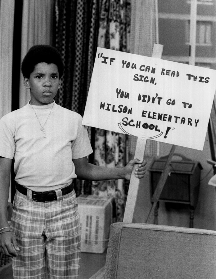 Michael Evans (Ralph Carter) carries a picket sign criticizing the quality of education at his school, in this still from the TV show <i>Good Times</i>.